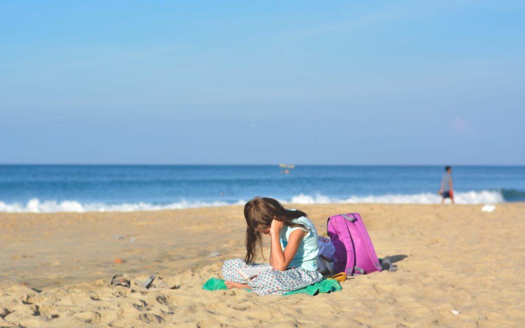 Deze betweter / boekenwurm leest zelfs nog op het strand!