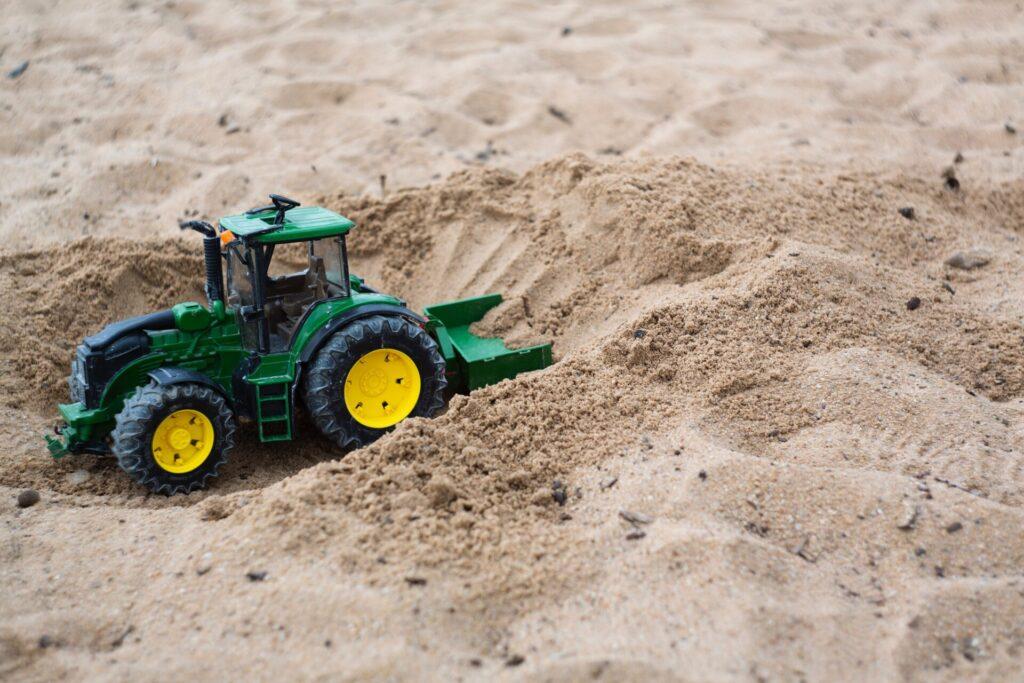 Een tractor in de zandbak.